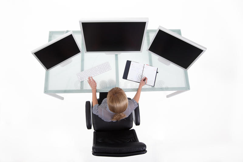 Bussines woman in her office upper view. Businesswoman in his clean high tech office looking on the monitors upper view royalty free stock photos