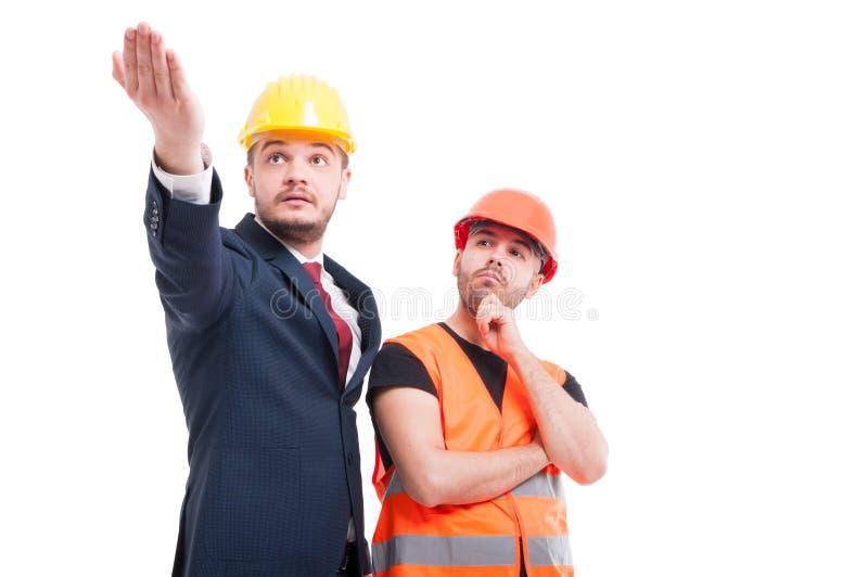 Bussinesman die iets verklaren aan jonge bouwer stock foto