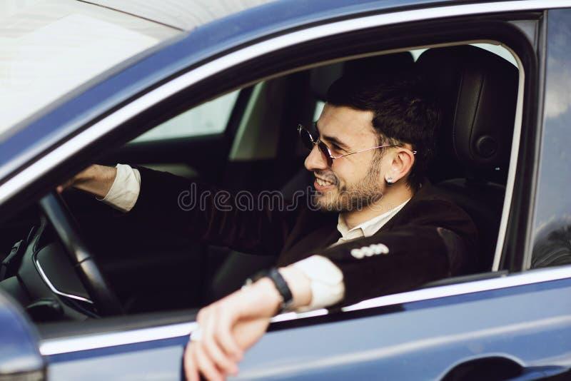 Bussinesman novo no terno e nos vidros pretos que conduzem seu carro Olhar do neg?cio Movimenta??o do teste do carro novo imagem de stock royalty free