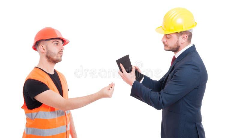 Bussinesman som betalar den unga byggmästaren eller konstruktörn royaltyfria bilder
