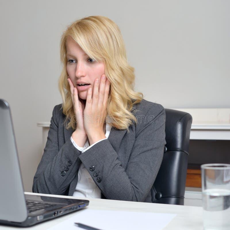 Bussiness妇女被震惊看她的膝上型计算机 免版税图库摄影