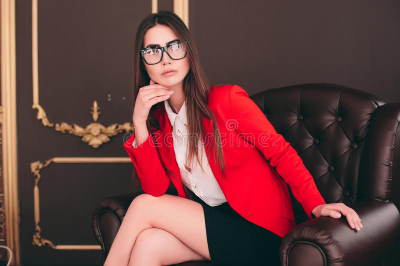 Bussiness boss girl in chair waiting to interview people. Young bussiness boss girl in chair waiting to interview people stock image