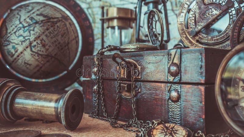 Bussola antica, collana dell'orologio, telescopio, contenitore di legno di tesoro e globo Pirate Collection Photos di modello fotografie stock