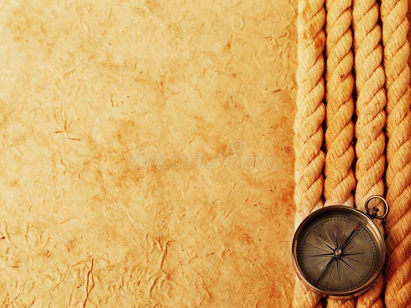 Bussola d'ottone antica con la corda su vecchio fondo di carta d'annata Retro stantio immagini stock libere da diritti