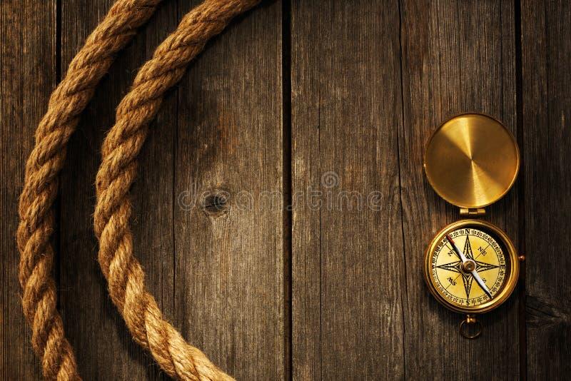 Bussola e corda antiche sopra fondo di legno immagine stock libera da diritti
