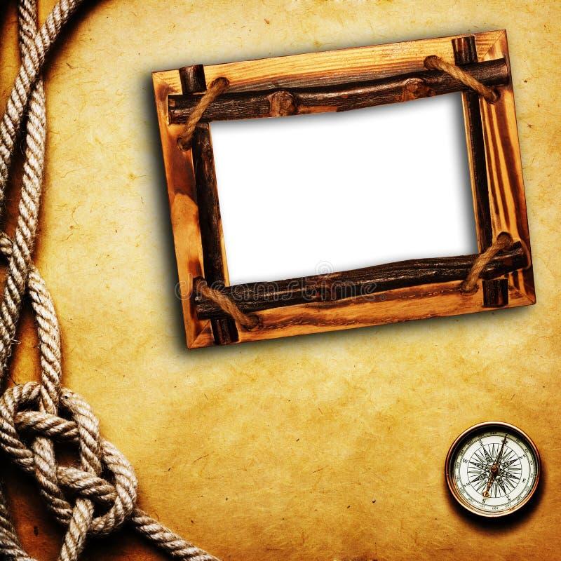 Bussola e corda sulla priorità bassa del grunge fotografia stock