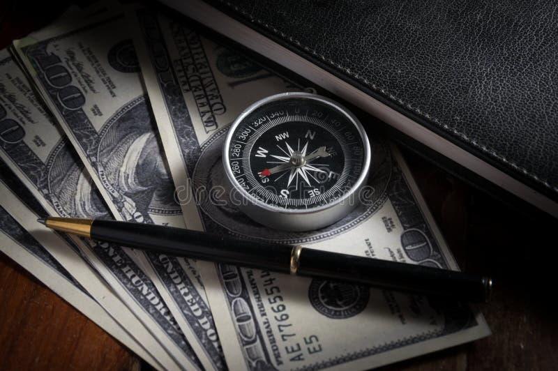 Bussola e penna su soldi con il libro fotografia stock