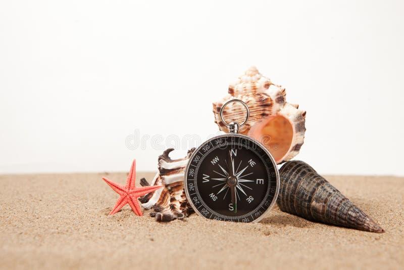 Bussola, seastar e conchiglie in primo piano della sabbia immagini stock libere da diritti