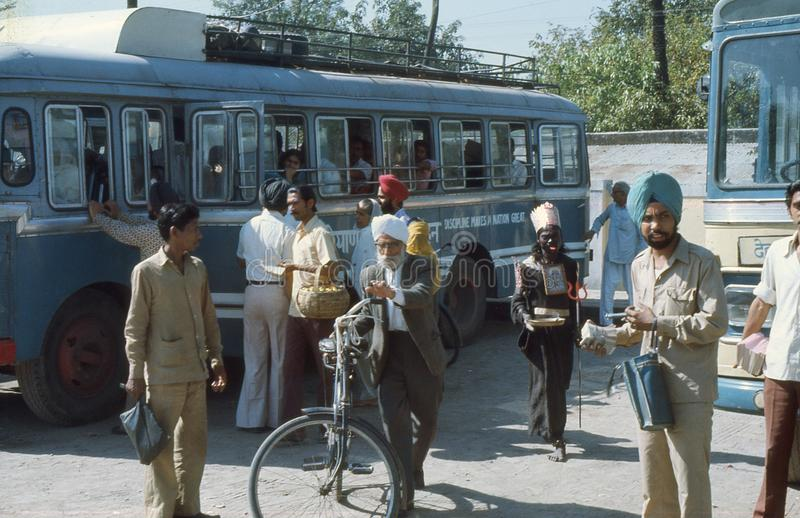 1977. India. Busstation. Waiting for departure. At the bus station in Chandigarh, India. Showing a mix of people, bus conductors, passengers and a holy beggar stock photos