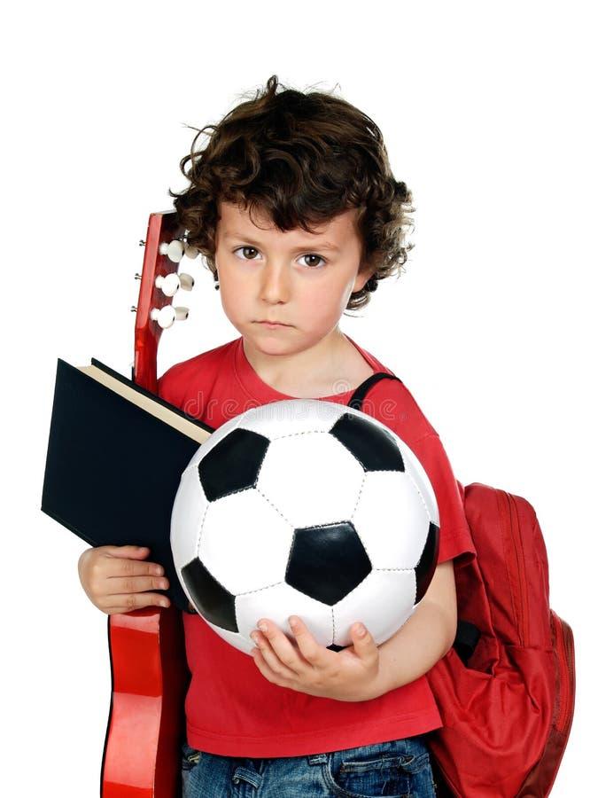 Bussy-Schulkind mit einem Ball, einer Gitarre und einem Buch stockfotos