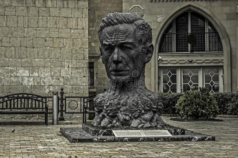 Bust of a poet with the characters of his works on it stock photo