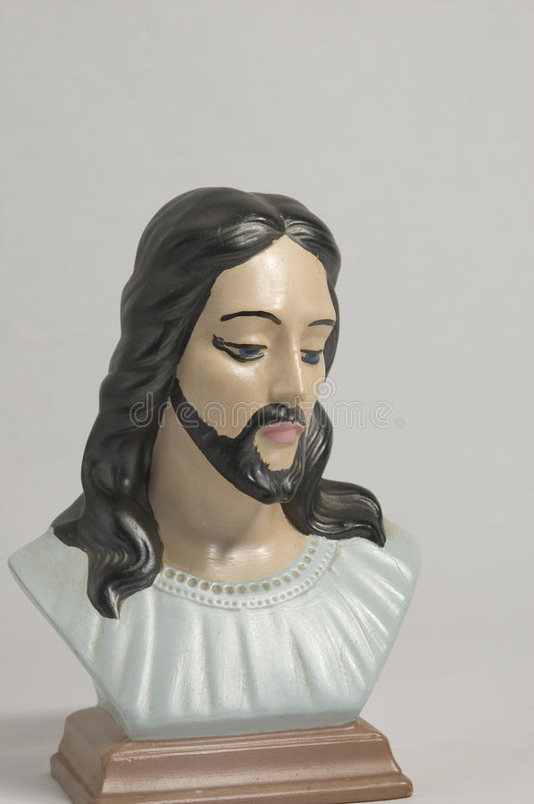 Bust of Jesus. A hand painted bust of Jesus looking down with long black hair and blue eyes stock photography