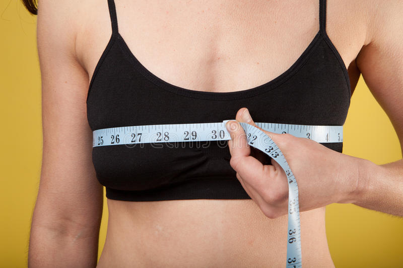 Bust measurement. Woman measuring her bust size with a black sport bra stock photos