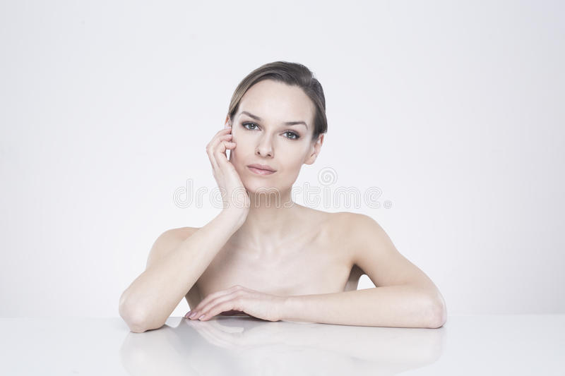 Bust of naked woman. Sitting front with her elbows leaned on the smooth surface royalty free stock image