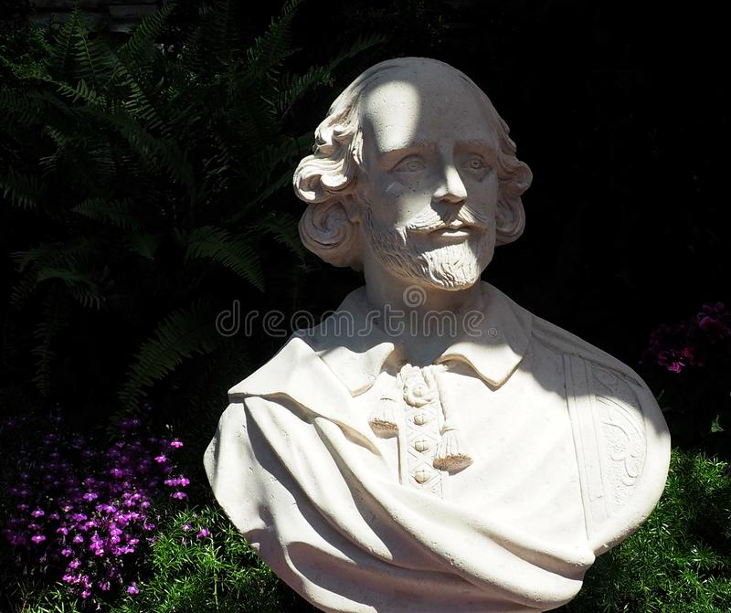 Bust Of William Shakespeare. With plants and flowers royalty free stock photo