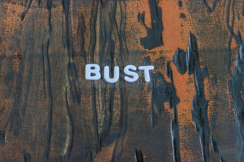 Bust written in white lettering. On weathered dark wood stock image
