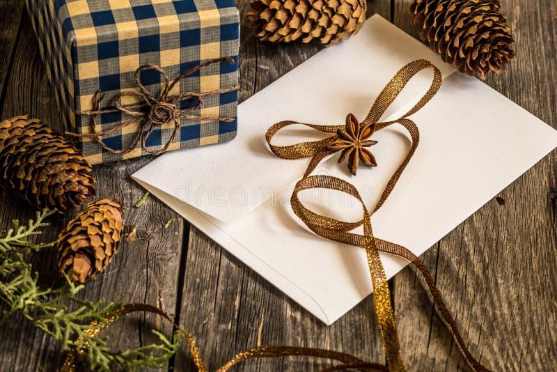 Busta bianca su fondo di legno con le pigne ed il regalo di Natale fotografia stock libera da diritti