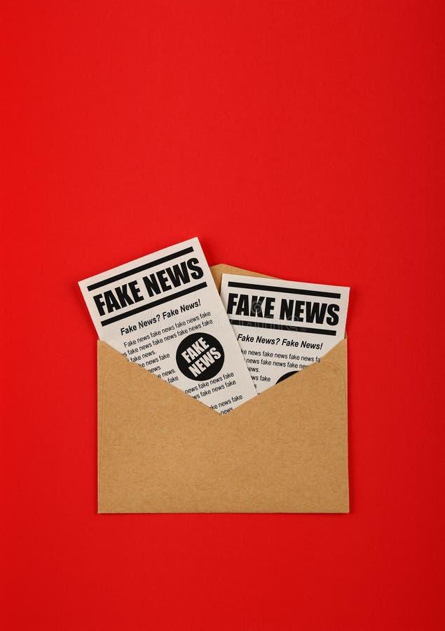 Busta con i giornali FALSI di NOTIZIE sopra rosso fotografia stock