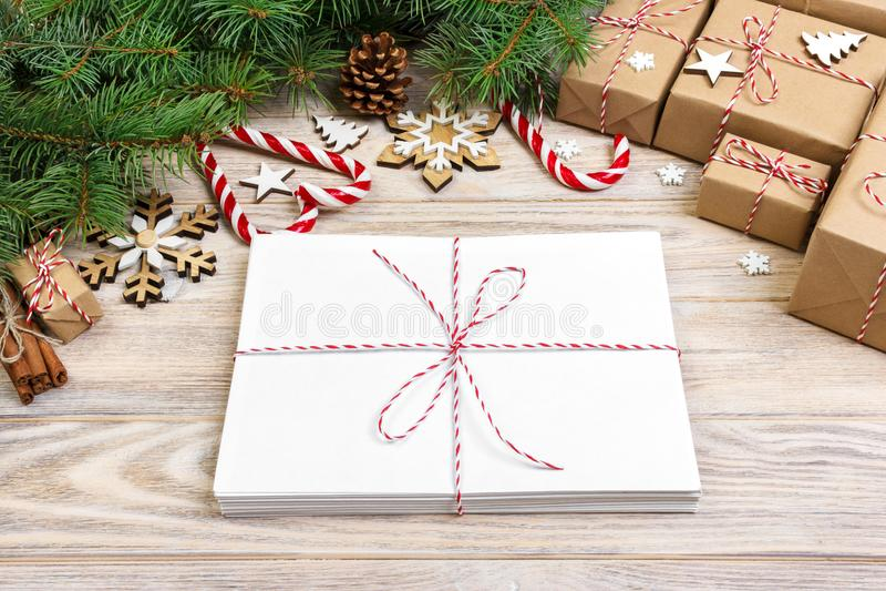 Busta con il foglio bianco di carta sul fondo di Natale - ramo dell'abete, pigne, nastro rosso, stella e cuore dei dolci Spazio f immagini stock libere da diritti