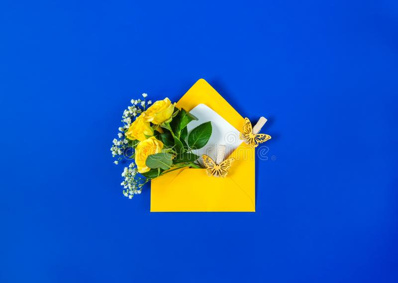 Busta con le rose gialle ed il Gypsophila bianco dei fiori del riempitore su fondo blu luminoso Vista superiore, disposizione pia fotografia stock