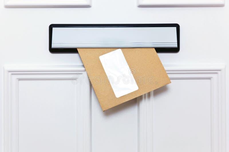 Busta del Brown in un letterbox delle entrate principali immagine stock