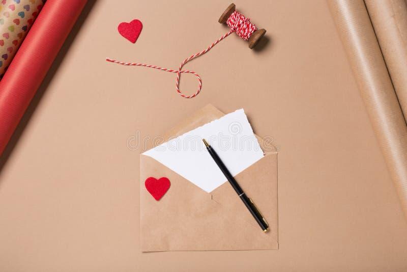 Busta del mestiere con cuore rosso, carta in bianco e la penna sulla tavola beige spostamento Concetto di amore Concetto di giorn fotografia stock