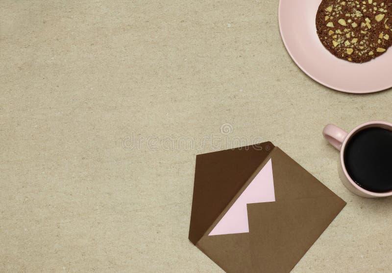 Busta del mestiere di Brown con lo spazio in bianco, tazza di caffè, dolce su fondo beige immagini stock