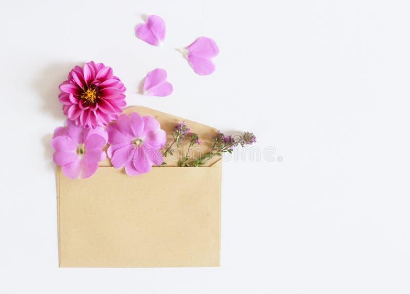 Busta di Brown con una disposizione dei fiori della molla su fondo bianco Disposizione piana, vista superiore Spazio vuoto per il immagini stock libere da diritti