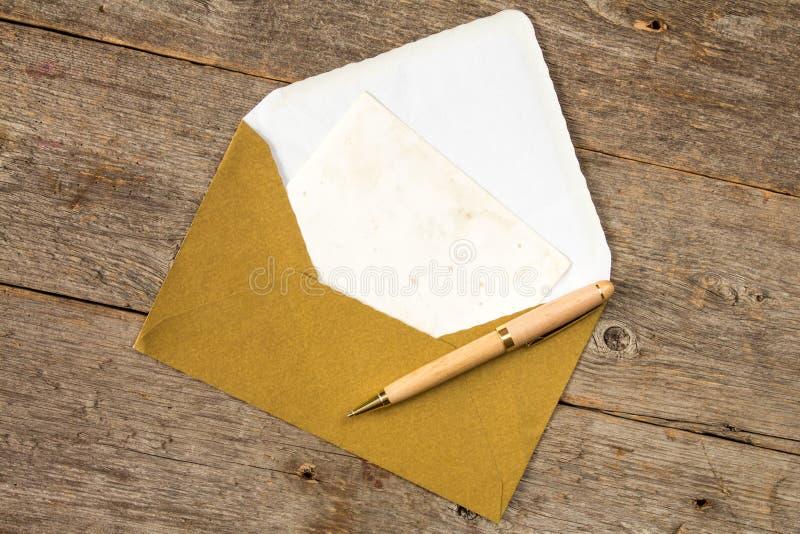 Busta dorata, carta in bianco e penna immagine stock