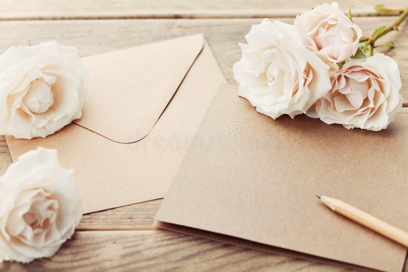 Busta o lettera, carta di carta e fiori rosa dell'annata sulla tavola di legno rustica per accogliere il giorno della donna o del fotografie stock