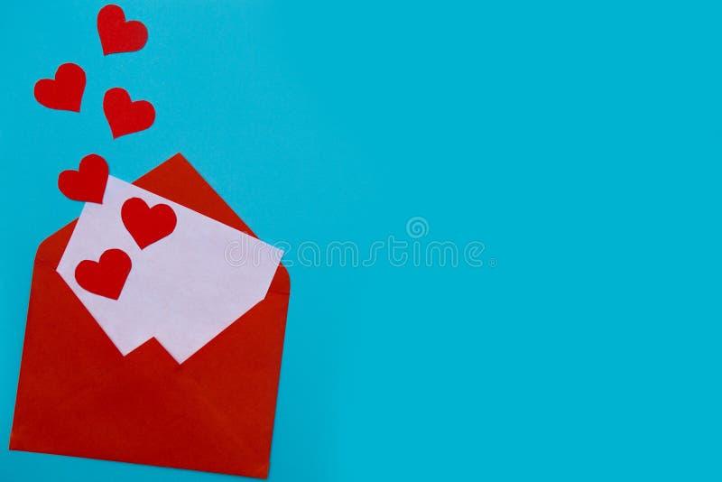 Busta rossa con la lettera di amore sopra fondo blu con molti cuori intorno fotografie stock