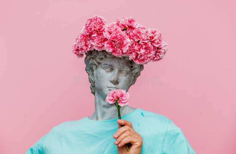 Buste antique de masculin avec le bouquet d'oeillets dans un chapeau images stock