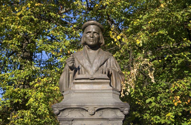 Buste de Mikael Agricola à l'arrière-plan du feuillage d'automne Vyborg photographie stock libre de droits