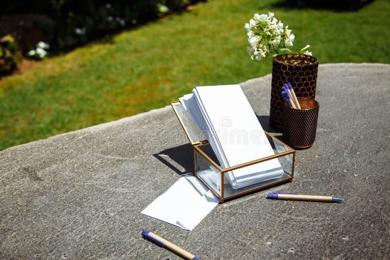 Buste per le richieste, le penne ed i fiori sulla tavola di pietra immagini stock