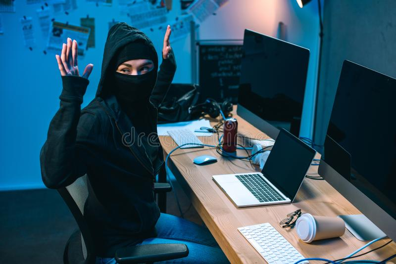 busted hacker in mask with raised hands in front royalty free stock image