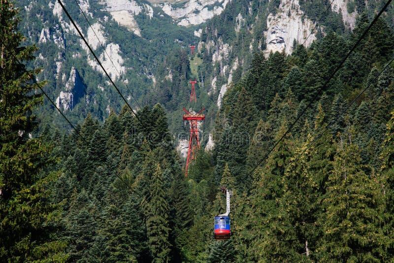 BUSTENI, RUMANIA - 2 DE AGOSTO DE 2017: La cabina azul del teleférico transporta a turistas del centro turístico de Busteni hasta imagenes de archivo