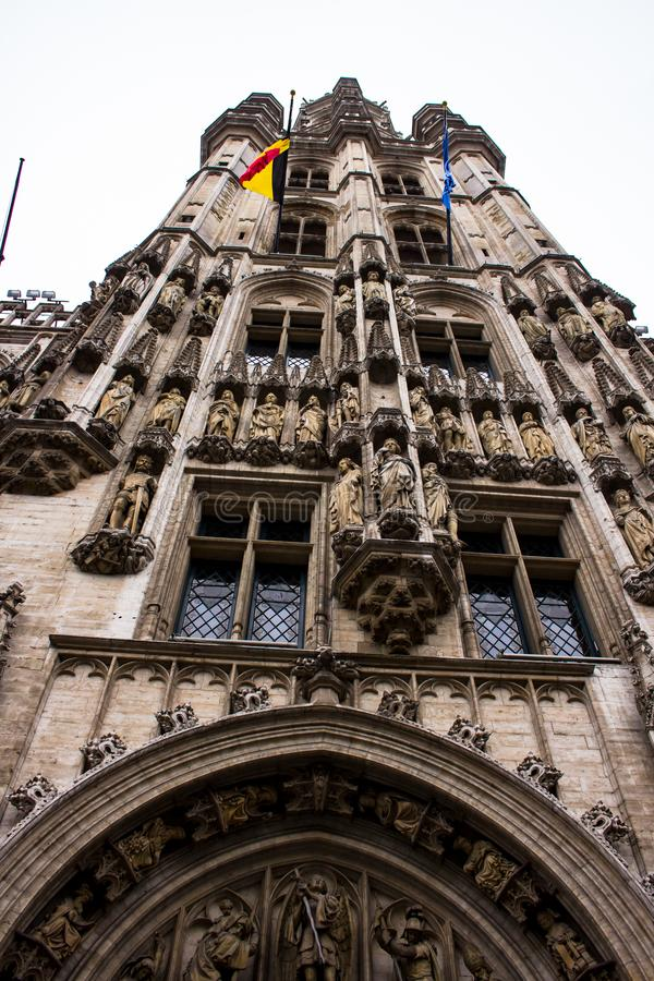 Building detail in Grand Place. Bustling Brussels Grand-Place centers on its namesake square, towered over by the Gothic City Hall and ringed by opulent guild stock photo