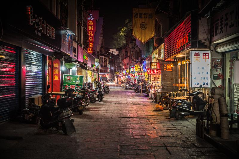 Neon-lit backstreet full of local shops late at night in Yangshuo China royalty free stock photo