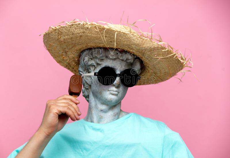 Busto antigo de masculino no chap?u com gelado no fundo cor-de-rosa imagens de stock