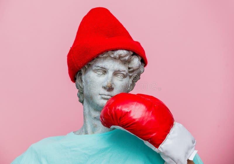Busto antiguo de masculino en sombrero con el guante de boxeo en fondo rosado fotos de archivo