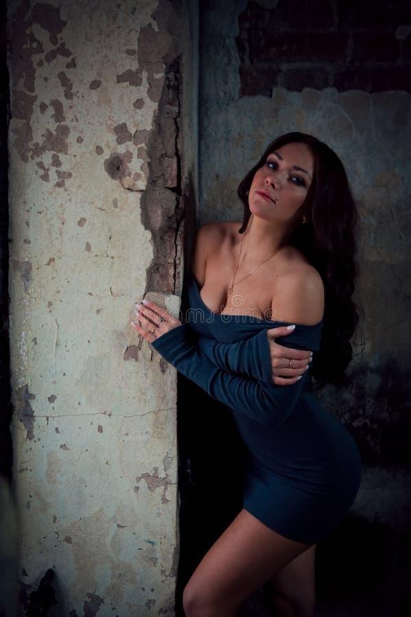 Busty seksowna brunetka w krótkiej sukni na ściennym tle fotografia royalty free
