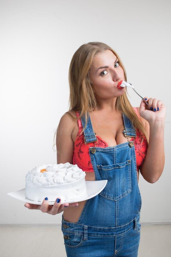 Busty sexy Mädchen, das Kuchen mit Schlagsahne isst stockbilder
