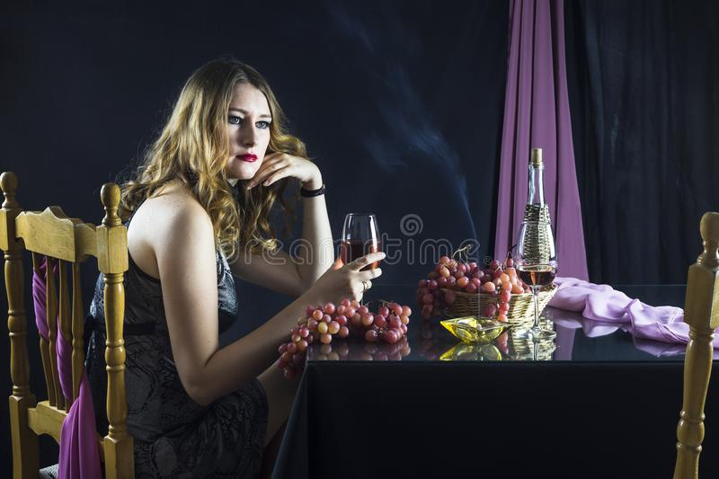 The girl with glass of wine. Busty young girl sitting at the table and holding a glass of wine on a black background stock photography
