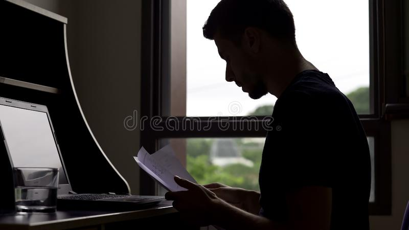 Busy account manager working all day at laptop, freelancer working with papers. Stock photo royalty free stock photography