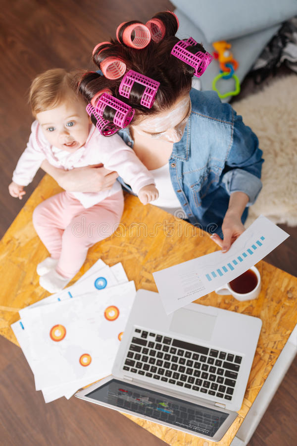 Busy active mom doing many things at the same time. Reading some documents. Enterprising hardworking inspiring mother spending the morning looing after her child royalty free stock photo