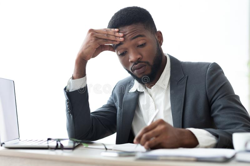 Busy african american businessman signing contracts or agreements at workplace. Busy businessman in formal suit signing contracts or agreements at workplace in royalty free stock photography