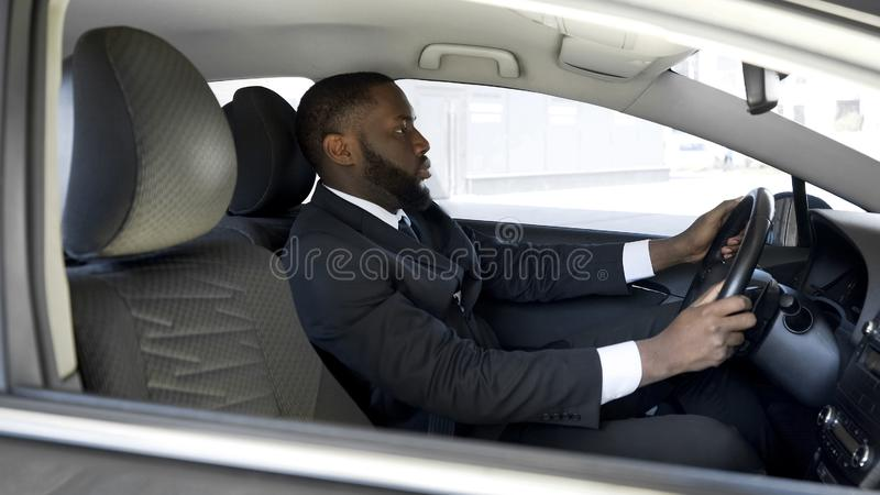 Busy Afro-American man in expensive suit driving to business meeting by car. Stock photo stock image