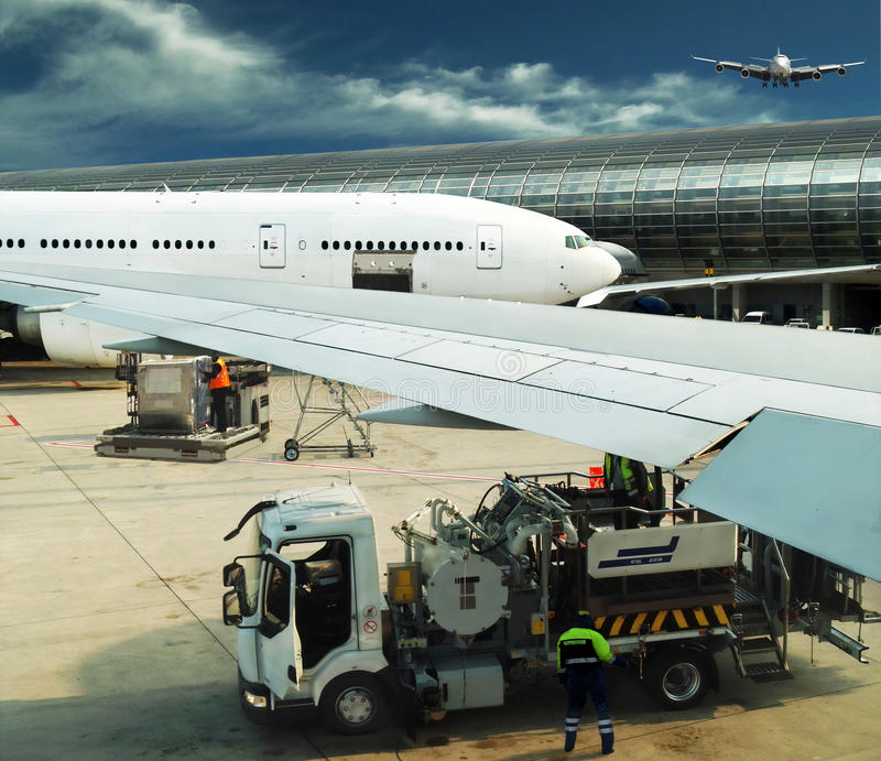 Busy airport. It is hard time of the modern airport. Supervisor is controlling maintenance, baggage (cargo) loading and refueling of parked airplanes. Another royalty free stock photos