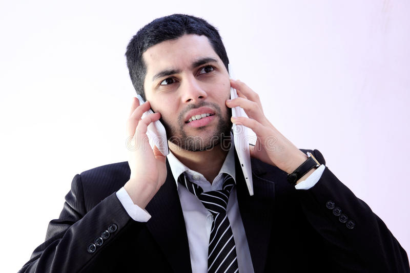 Busy arab business man. Image of busy arab business man wearing black suit and talking wih 2 phones stock photos