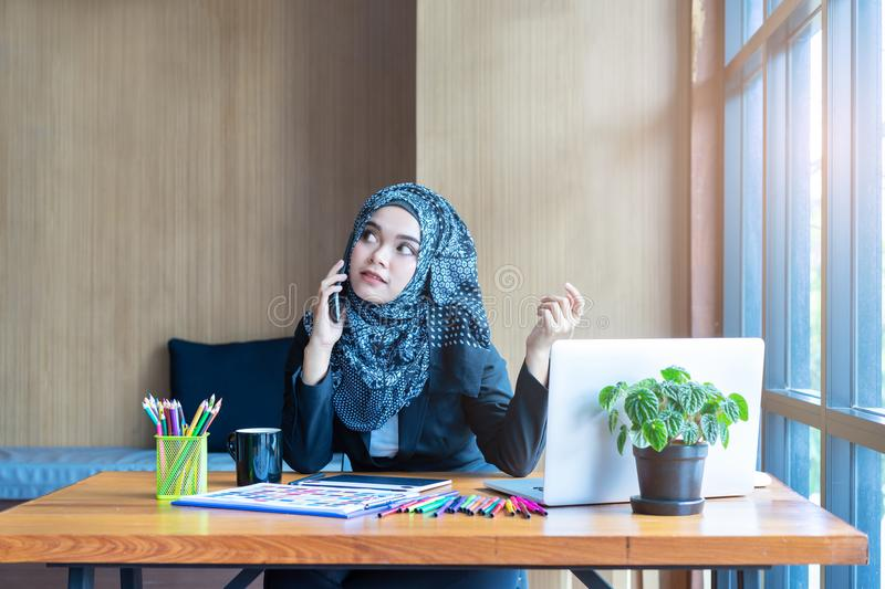 Busy asian muslim business woman talking on mobile phone stock image